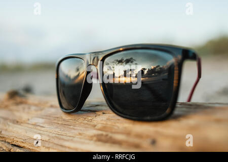 Sunglasses and Hugging Couple in Reflection from Glasses. Honeymoon on Beach. - Stock Photo