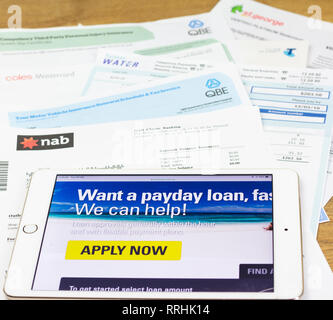 iPad and bills of Australian consumer looking at pay day lender site to pay household bills. Debt-stressed consumers are turning to payday finance. - Stock Photo