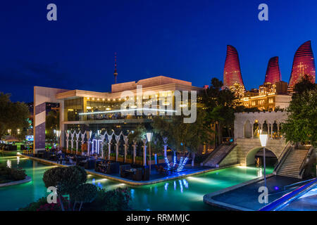 Evening view of central city park with neon highlighted buildings and skyscrapers, Baku, Azerbaijan - Stock Photo