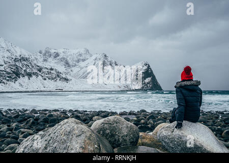 Woman in warm clothing enjoying remote snowy ocean and mountain view, Lofoten Islands, Norway - Stock Photo
