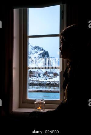 Pensive woman looking out window at snowy mountain, Reine, Lofoten Islands, Norway - Stock Photo