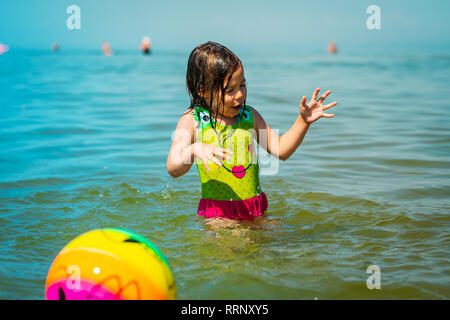 little girl gets wet after playing a ball in the sea in the summer - Stock Photo