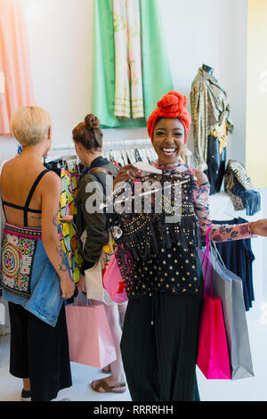 Portrait happy, enthusiastic young woman shopping in clothing store - Stock Photo