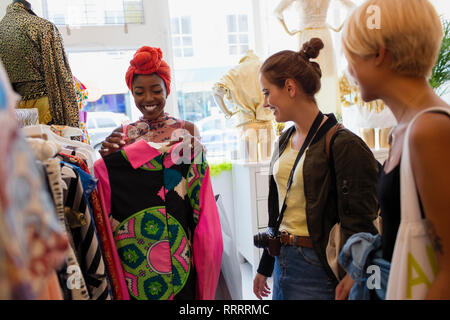 Young woman friends shopping in clothing store - Stock Photo