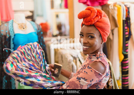 Portrait smiling, confident young woman in headscarf shopping in clothing store - Stock Photo