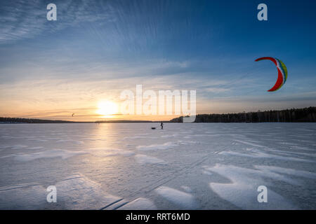 Kite skiing on frozen lake with beautiful sunset at winter evening in Finland - Stock Photo