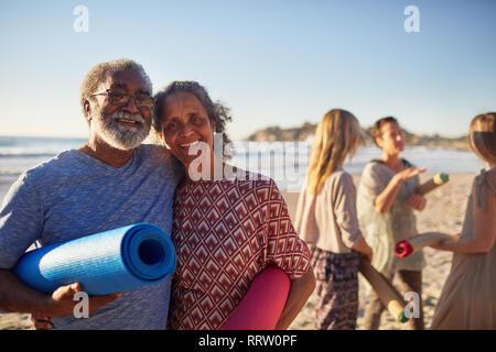 Portrait happy senior couple with yoga mats on sunny beach during yoga retreat - Stock Photo