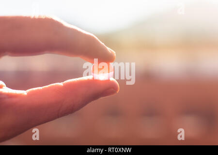 Water gel balls. Small gel ball in the hand at sunrise. Polymer gel. Silica gel. Balls of hydrogel. Crystal liquid ball with reflection. Texture backg - Stock Photo