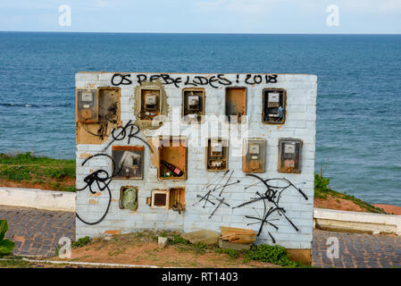 Old and broken electric meter boxes on a wall in front of the sea on Brazil - Stock Photo