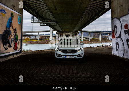 SUV Kia Sportage 2.0 CRDI awd or 4x4, white color, parked under the bridge, on the banks of the river Sava. - Stock Photo