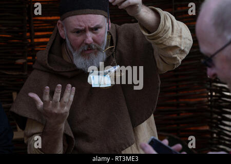 Man dressed in Viking clothes and weighing money with old scales at a Viking Festival in York,England. - Stock Photo
