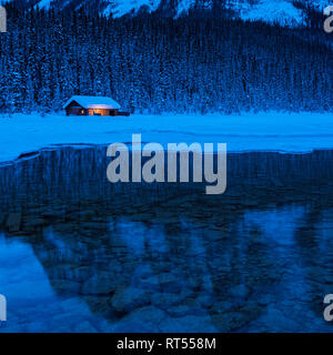 Cabin on the edge of a pine forest on the shore of Lake Louise in Winter during the blue hour before dawn, Banff National Park, Alberta, Canada - Stock Photo