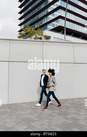 Two happy colleagues walking outside office building - Stock Photo
