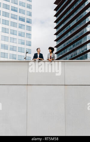 Two colleagues talking outside office building - Stock Photo