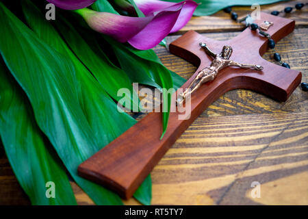Cross with jesus christ on a wooden background with a purple calla and chaplet - religious easter lent concept - Stock Photo