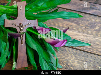 Cross with jesus christ on a wooden background with a purple calla - religious easter lent concept background - Stock Photo