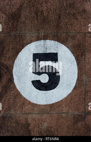 Number Five Door Number Painted In Black Within A White Circle On A Pink Stone Wall - Stock Photo