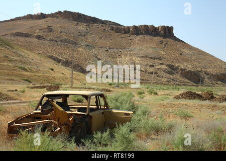 A crashed empty abandoned car in field - Stock Photo