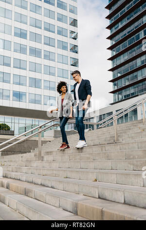 Two colleagues walking and talking on stairs outside office building in the city - Stock Photo