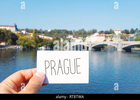 closeup of the hand of a caucasian man with a signboard with the wort Prague, in front of the Vltava River in Prague, Czech Republic, with the Manes b - Stock Photo