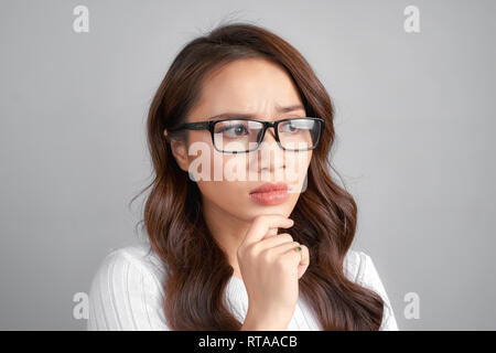 Hmm. Suspicious thoughtful young race female looking up, keeping hand on her face as if trying hard to remember something important. Human face expres - Stock Photo