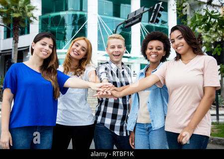 Group of mutliethnic young adult people building a team outdoor - Stock Photo