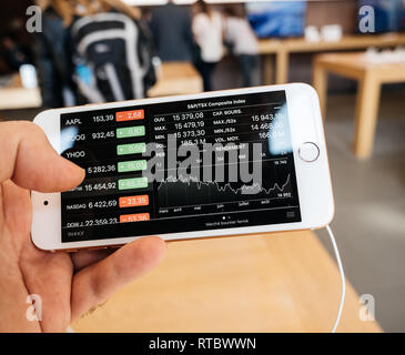 PARIS, FRANCE - SEP 22, 2017: New iPhone 8 and iPhone 8 Plus, as well the updated Apple Watch, Apple TV goes on sale today in Apple Store with customer looking at standard and poor's composite index, - Stock Photo