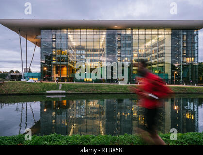 STRASBOURG, FRANCE - SEP 19 2017: Man silhouette  jogging along the canal with Council of Europe Agora building in the background at dusk - Stock Photo