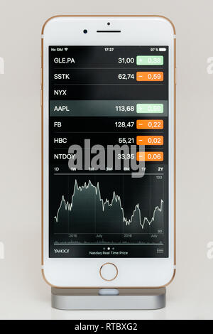PARIS, FRANCE - SEP 26, 2016: New Apple iPhone 7 Plus in docking station after unboxing and testing by installing and running the app application software Apple Stock Market Price with AAPL quotation - Stock Photo