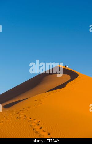 Woman walking up the giant sanddune Dune 45, Namib-Naukluft National Park, Namibia - Stock Photo