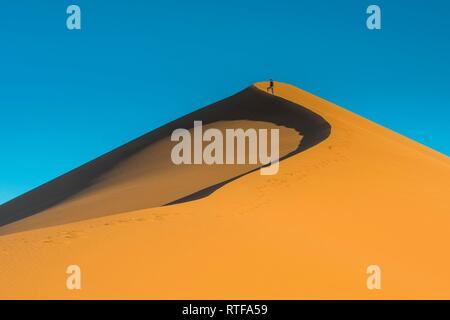 Woman on the giant sanddune Dune 45, Namib-Naukluft National Park, Namibia - Stock Photo