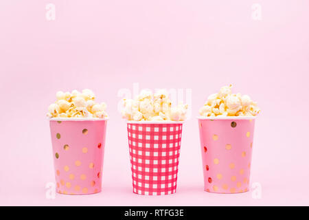 several cups of popcorn on a pink background Copy space - Stock Photo
