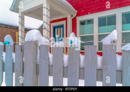 Wooden fence with lights and snow in Daybreak Utah. White wooden fence of a colorful home in Daybreak, Utah. The fence is lined with lights and topped - Stock Photo