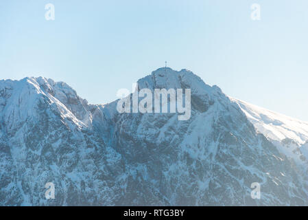 A beautiful view of the Polish Tatra Mountains. Sunny, beautiful day in the winter, snow-capped mountains and blue sky. A visible metal cross on the t - Stock Photo