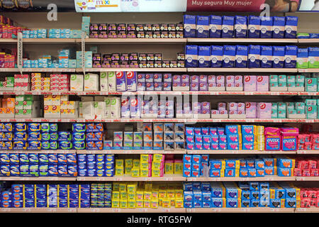Stack of plastic disposable sanitary towels tampons and pads displayed on a supermarket - Stock Photo