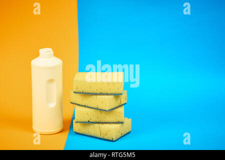 means for washing dishes and sponges on a colored background. household chores - Stock Photo