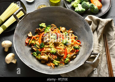 Udon stir-fry noodles with vegetables in wok pan on black stone table. Stir fried vegetables with noodles in asian style. - Stock Photo