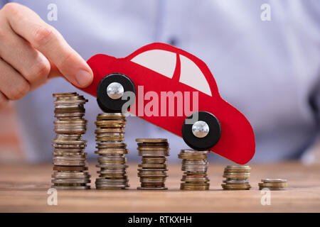 Close-up Of A Person's Hand Holding Car Over Declining Stacked Coins - Stock Photo
