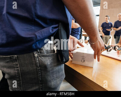 PARIS, FRANCE - SEP 22, 2017: New iPhone 8 and iPhone 8 Plus, as well the updated Apple Watch, Apple TV goes on sale today in Apple Store with Apple Genius holding Apple Watch box  - Stock Photo