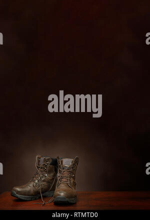 Vertical shot of a pair of old work boots on a brown background with copy space.  The boots are in the lower left hand corner. - Stock Photo
