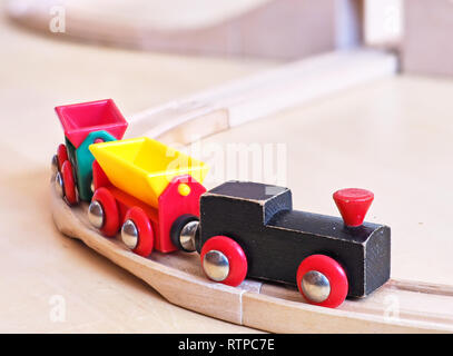 Wooden toy train running on miniature tracks. The black engine pulling colorful cars on the floor. Educational toys for children in preschool and kind - Stock Photo
