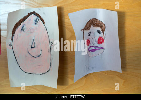 hanging artwork of Childs coloured cute portraits crayon drawing on paper stuck on a wall - Stock Photo