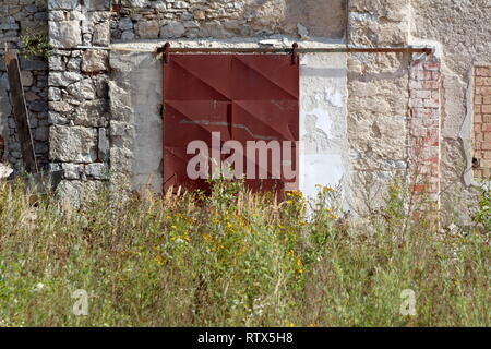 Rusted metal sliding warehouse doors mounted on old dilapidated wall with tall grass and small flowers in front at abandoned industrial complex - Stock Photo