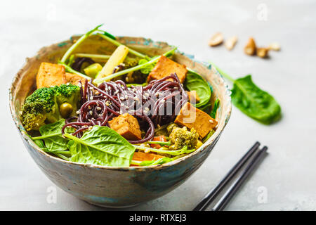 Asian vegan stir fry with tofu, rice noodles and vegetables - Stock Photo