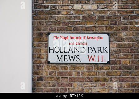London, UK - February 23, 2019: Holland Park Mews street name sign on a wall in The Royal Borough of Kensington and Chelsea, an affluent area in West  - Stock Photo
