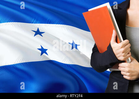 Learning Honduran language concept. Young woman standing with the Honduras flag in the background. Teacher holding books, orange blank book cover. - Stock Photo