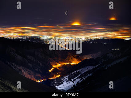 Almaty city lights at foggy winter night view from the mountains, Kazakhstan, Central Asia. - Stock Photo