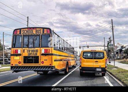 Beautiful view of Yellow School Bus and Taxi on the streets of Orlando, Florida, USA. - Stock Photo