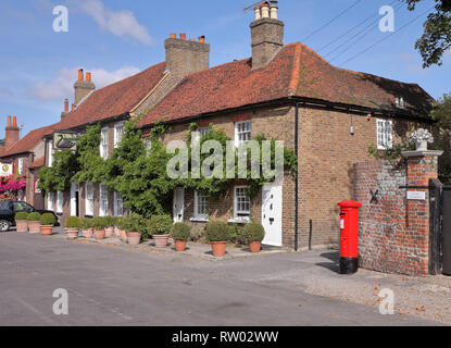 Traditional English Village Pub with red post box outside - Stock Photo