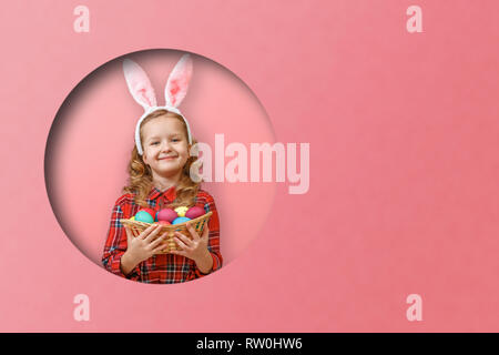 Cute little child girl with bunny ears holding basket of Easter eggs. Child in a round hole circle in colored pink background - Stock Photo